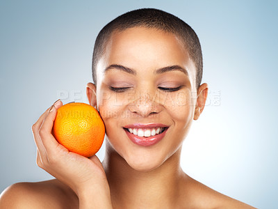 Buy stock photo Studio shot of a beautiful young woman posing with an orange against a blue background