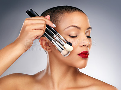 Buy stock photo Studio shot of a beautiful young woman posing with a set of makeup brushes