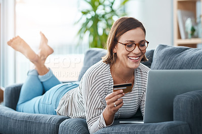 Buy stock photo Full length shot of a young woman using her laptop and credit card on the sofa at home