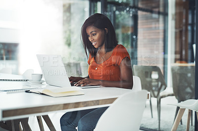 Buy stock photo Shot of an attractive young businesswoman working on a laptop at her office desk