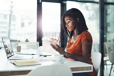 Buy stock photo Shot of an attractive young businesswoman using her digital tablet at her office desk at work