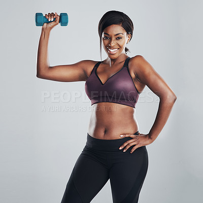 Buy stock photo Studio portrait of an attractive and fit young woman exercising with a dumbbell against a grey background