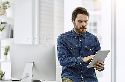 Buy stock photo Cropped shot of a young businessman using a digital tablet in his office