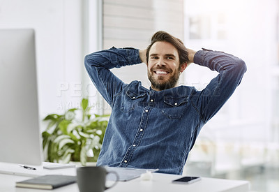 Buy stock photo Shot of a young businessman relaxing with his hands behind his head in his office