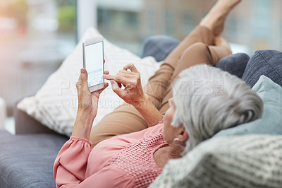 Buy stock photo High angle shot of a mature woman using her cellphone while relaxing on a sofa at home