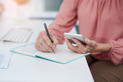 Buy stock photo Shot of an unrecognizable mature woman writing down details from her cellphone to her diary at work