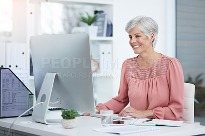 Buy stock photo Shot of a cheerful mature businesswoman working on a computer in her office