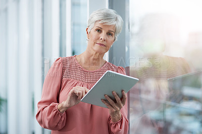 Buy stock photo Portrait of a mature businesswoman using her digital tablet at work
