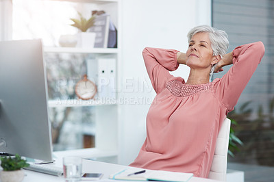 Buy stock photo Shot of a mature businesswoman laying back and relaxing in her chair at work