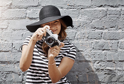 Buy stock photo Shot of a young woman taking a picture with her camera against a brick wall outdoors