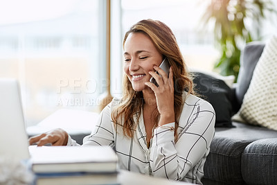 Buy stock photo Shot of attractive businesswoman taking a phone call while doing some work on her laptop at home