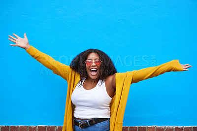Buy stock photo Cropped shot of a happy young woman celebrating against a blue background