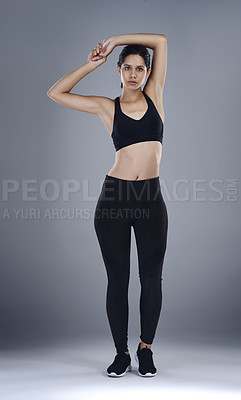 Buy stock photo Full length shot of a sporty young woman standing and posing against a grey background