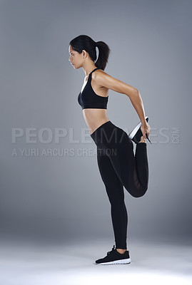 Buy stock photo Full length shot a sporty young doing her stretching exercises against a grey background