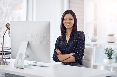 Buy stock photo Portrait of an attractive young businesswoman posing with her arms folded in her office desk at work