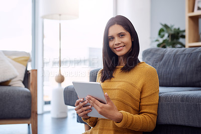 Buy stock photo Portrait of an attractive young woman using her digital tablet while relaxing in her living room at home