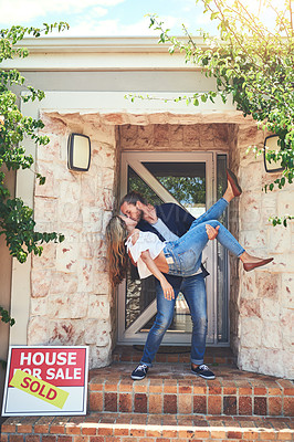 Buy stock photo Shot of an affectionate young couple celebrating the move into their new home
