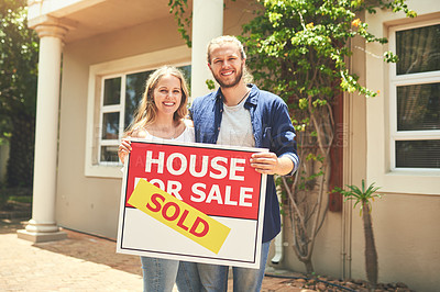Buy stock photo Portrait of a young couple holding a sign outside their new home
