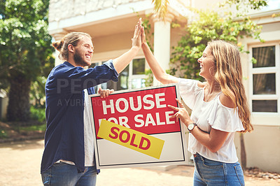 Buy stock photo Shot of a young couple giving each other a high five while holding a sign outside their new home