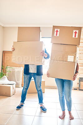 Buy stock photo Shot of a couple carrying a pile of boxes while moving house