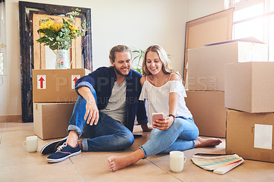 Buy stock photo Shot of a young couple using a cellphone while moving house
