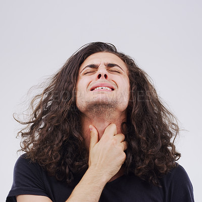 Buy stock photo Studio shot of a young man suffering with a sore throat against a grey background