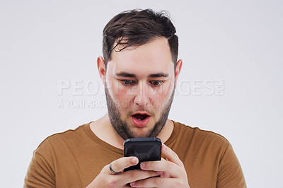 Buy stock photo Shot of a young man looking surprised while reading something on his cellphone