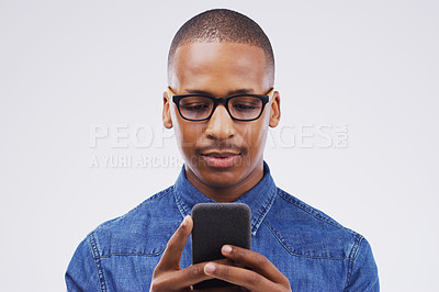 Buy stock photo Studio shot of a handsome young man using his cellphone