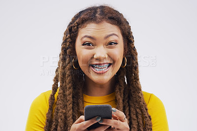 Buy stock photo Studio shot of a young woman looking excited while using her cellphone