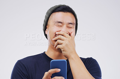 Buy stock photo Studio shot of a man laughing while using his cellphone