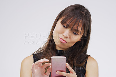 Buy stock photo Studio shot of a young woman using her cellphone against a grey background