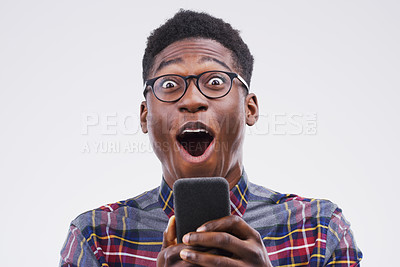 Buy stock photo Studio shot of a young man looking surprised while using his cellphone