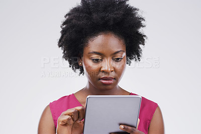 Buy stock photo Studio shot of a young woman using a digital tablet against a grey background