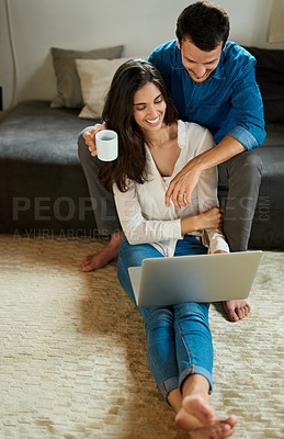 Buy stock photo Shot of a cheerful young couple using a laptop together while relaxing at home