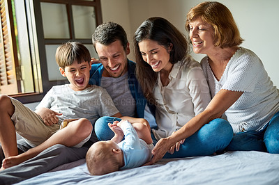 Buy stock photo Shot of a beautiful family bonding and enjoying themselves at home