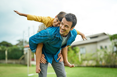 Buy stock photo Shot of a cheerful young father giving his son a piggyback ride outdoors