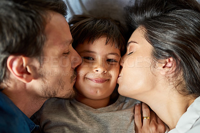 Buy stock photo Shot of a beautiful young couple kissing their young son on the cheeks at home