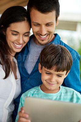 Buy stock photo Shot of a beautiful young couple and their son using a digital tablet together at home