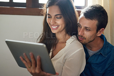 Buy stock photo Shot of an affectionate young couple using a digital tablet together at home