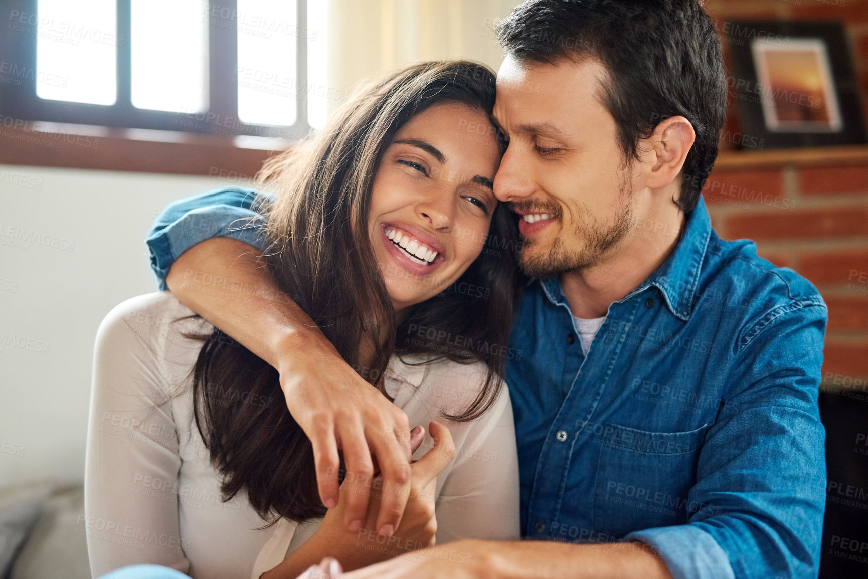 Buy stock photo Shot of an affectionate young couple spending some time together at home