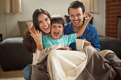 Buy stock photo Shot of a cheerful young couple and their son spending some time together at home