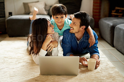 Buy stock photo Shot of a young couple and their son lying down on the carpet and using a laptop together at home