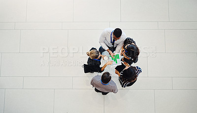 Buy stock photo High angle shot of a group of businesspeople using a digital tablet in a modern workplace