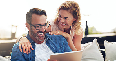 Buy stock photo Shot of an affectionate mature couple using a digital tablet while relaxing on a couch together outdoors