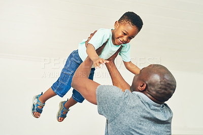 Buy stock photo Shot of a father playing with his little son at home