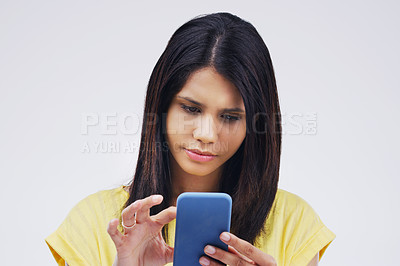 Buy stock photo Studio shot of a young woman using a mobile phone against a grey background