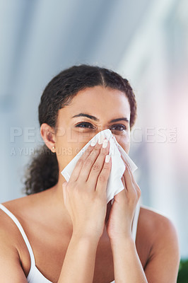 Buy stock photo Cropped shot of an attractive young woman blowing her nose in the bathroom at home