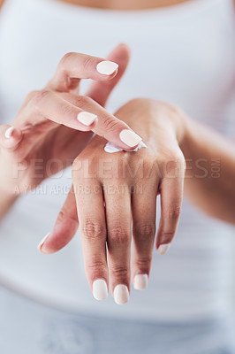 Buy stock photo Cropped shot of an unrecognizable woman applying moisturizer