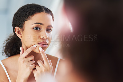Buy stock photo Cropped shot of a beautiful young woman squeezing a pimple in the mirror