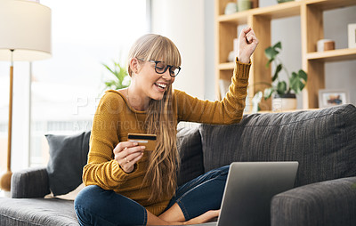 Buy stock photo Shot of a young woman cheering while using a laptop and credit card on the sofa at home
